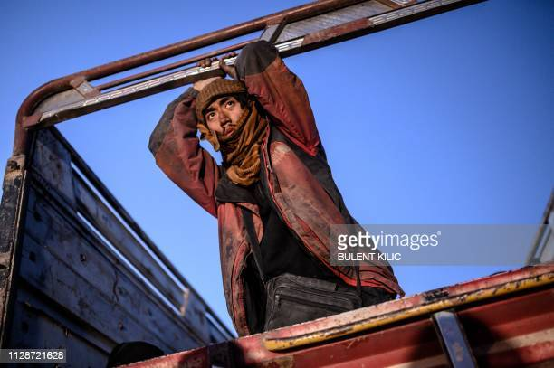 A man suspected of belonging to the Islamic State group who spoke to AFP journalists in French leans on the back of a truck as he waits to be...
