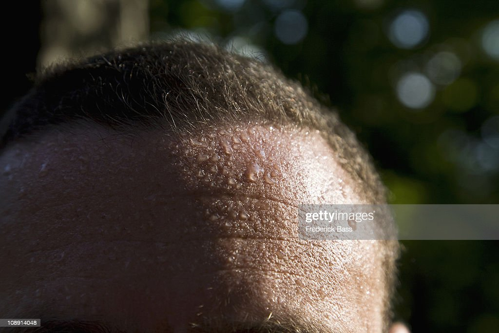 A man sweating, detail of forehead : Stock Photo
