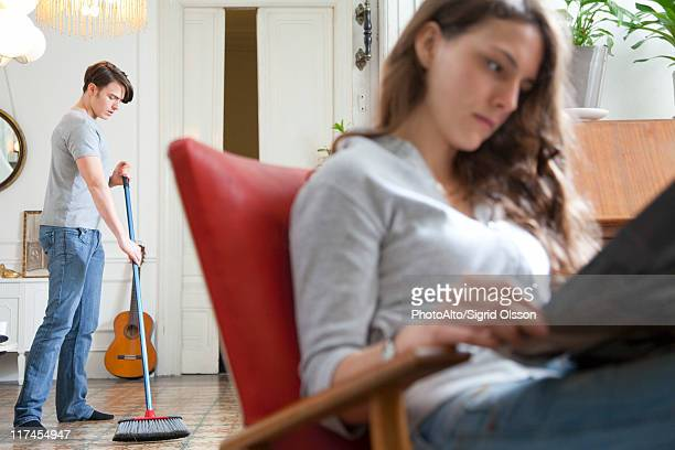 Man sweeping floor while wife reads