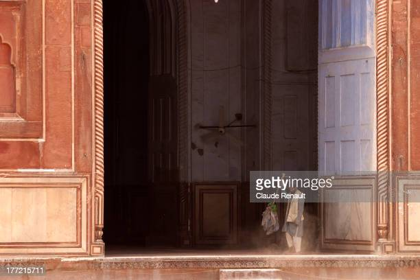 CONTENT] A man sweeping inside a Mosque in Agra