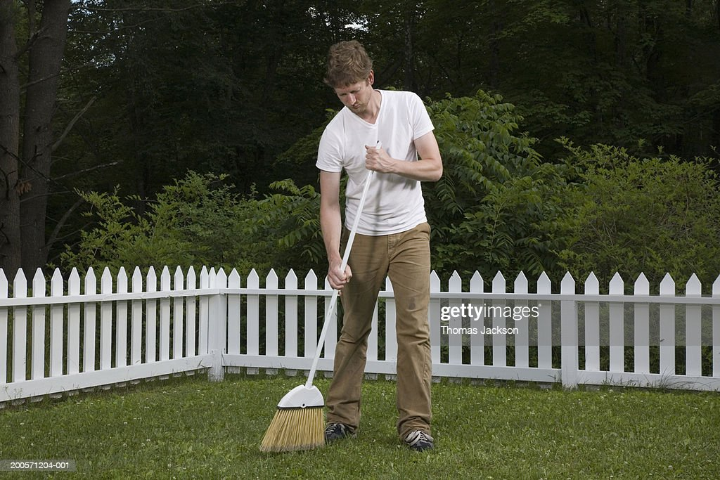 Man sweeping lawn with broom : Stock Photo