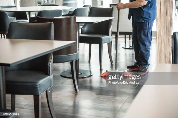 Man sweeping restaurant floor