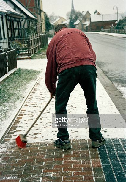 man sweeping snow on sidewalk - bending over stock pictures, royalty-free photos & images