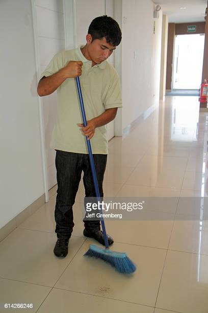 Man sweeping the floor in the hallway of 3B Barranco Bed and Breakfast