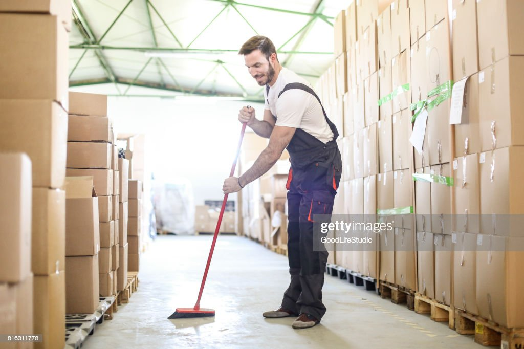 Man sweeping the warehouse floor : Stock Photo