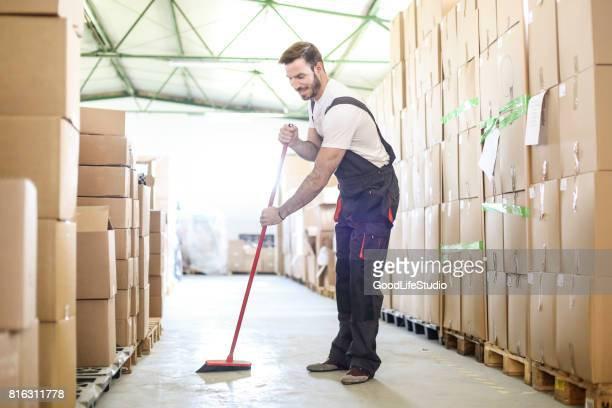 man sweeping the warehouse floor - commercial cleaning stock photos and pictures