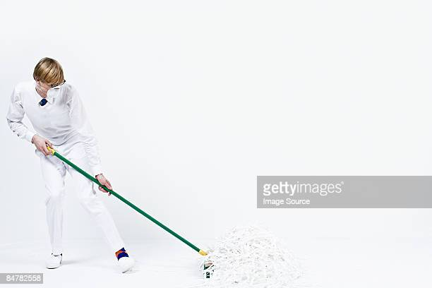 A man sweeping up shredded paper