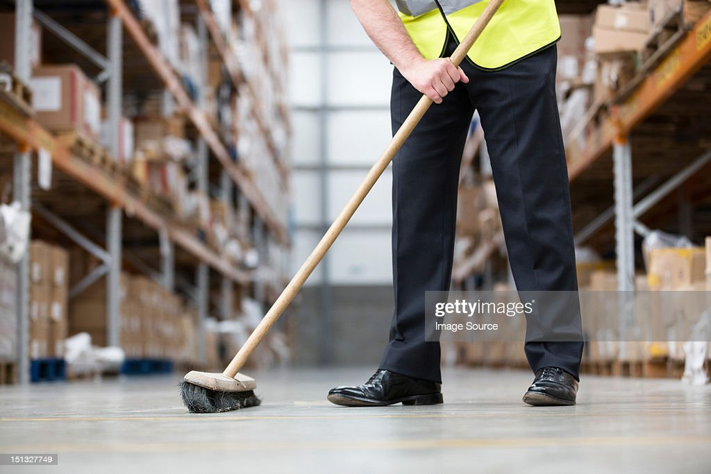 Man sweeping warehouse floor with broom : Stock Photo