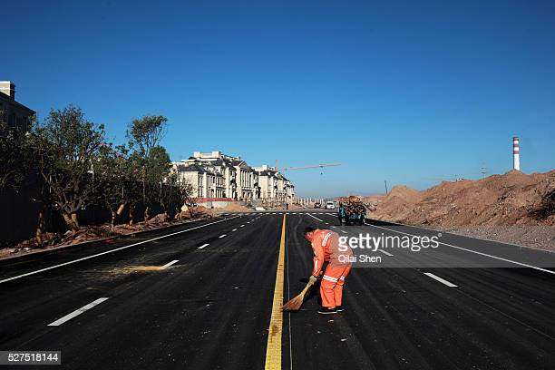 A man sweeps a newly built road leading towards a luxury housing develpment near the Kangbashi New District of Ordos City Inner Mongolia China on 16...