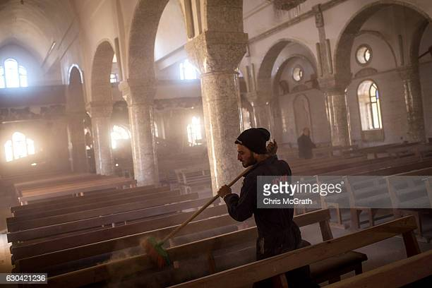 A man sweeps dust off seating in preparation for the Christmas Day mass at the Mar Hanna Church on December 22 2016 in Mosul Iraq After recently...