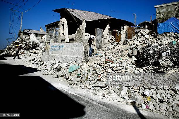 Man sweeps his front yard of dust and debris in the Bel Air neighborhood of Port au Prince Haiti on February 3 2010. Haiti was struck by a magnitude...