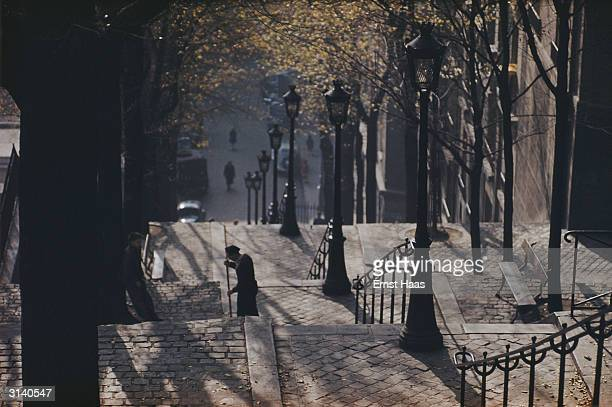 A man sweeps the autumn leaves from a long flight of steps leading up to Montmartre in Paris Colour Photography book