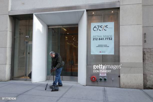 A man sweeps the sidewalk outside an empty store front on 5th Avenue on February 8 2018 in New York The New York borough of Manhattan is richer and...