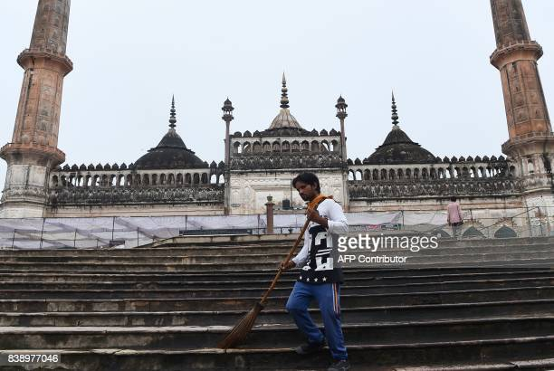 A man sweeps the stairs next to the mosque at the Bara Imambara a colossal imambara complex in Lucknow northern India on August 25 2017 / AFP PHOTO /...