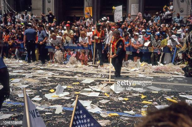 A man sweeps ticker tape from Broadway's Canyon of Heroes as a crowd of people stand behind NYPD barricades during a parade for Desert Storm veterans...