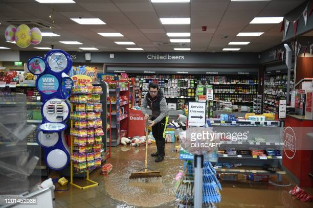 A man sweeps up flood water in a convenience store in Tenbury Wells in western England on February 17 left after the River Teme broke its banks and...