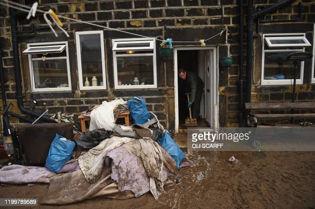 TOPSHOT A man sweeps water from a home in Mytholmroyd northern England on February 10 2020 after flooding brought by Storm Ciara Storm Ciara grounded...