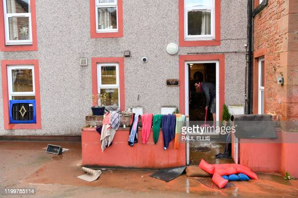 Man sweeps water out of a residential building in Appleby, northwest England, on February 10, 2020 after flooding brought by Storm Ciara. - Storm...