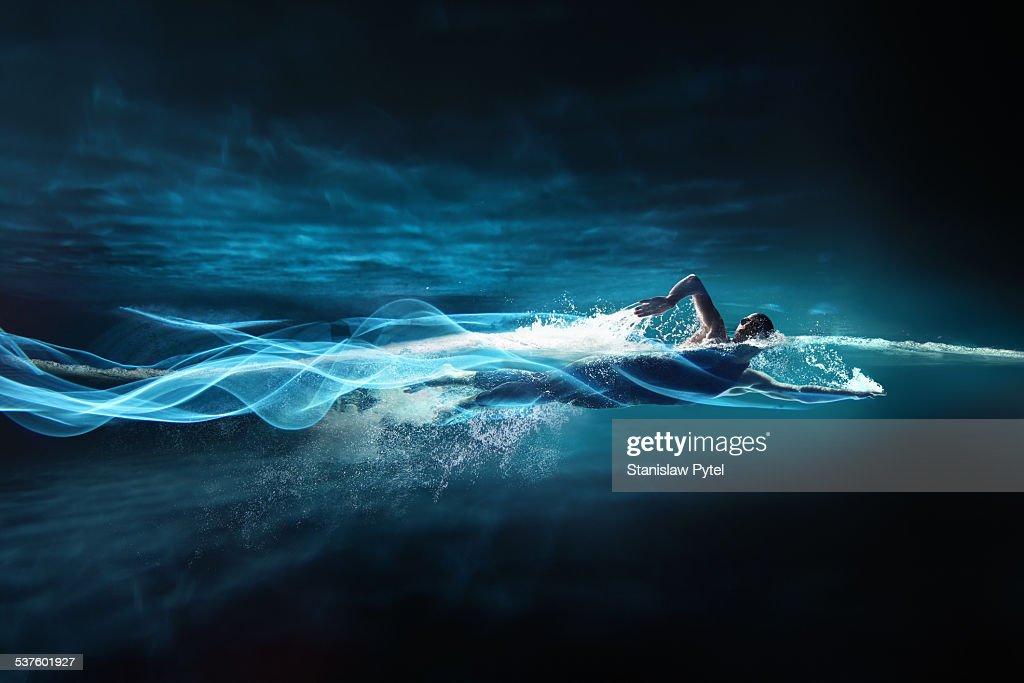 Man swimming crawl, leaving streaks of light : Stock Photo