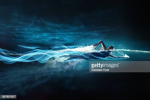 man swimming crawl, leaving streaks of light - image foto e immagini stock