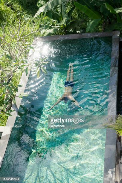 Man swimming diving under water in swimming pool
