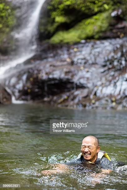 A man swimming in a rover smiling