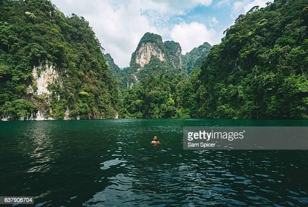 man swimming in epic jungle lake lagoon in khao sok, thailand - lagune stockfoto's en -beelden