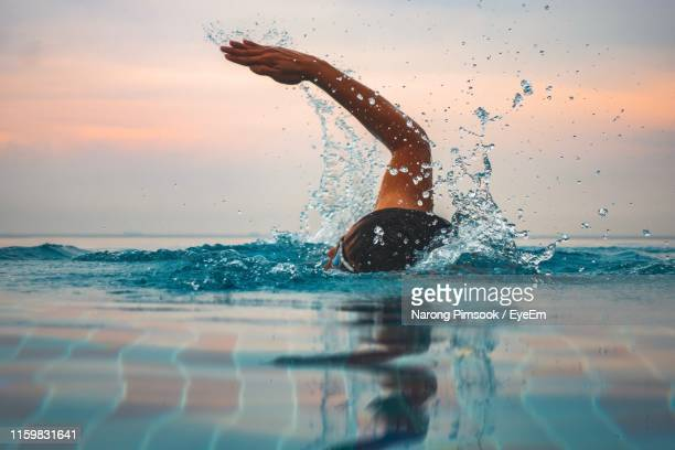 man swimming in infinity pool against sky during sunset - estilo de vida ativo imagens e fotografias de stock