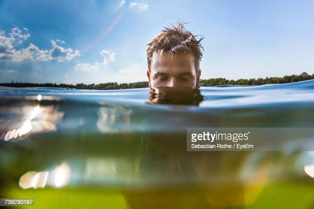Man Swimming In Lake Against Sky During Sunny Day