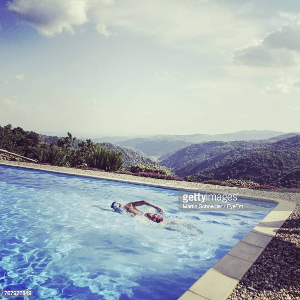 Man Swimming In Pool Against Mountains And Sky