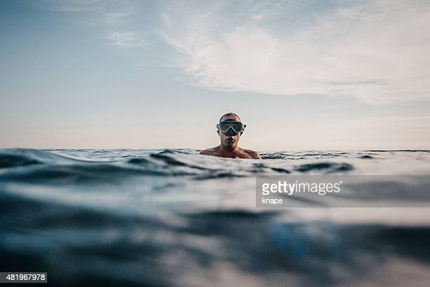 Man swimming in sea with scuba mask