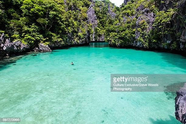 Man swimming in secluded lagoon surrounded by beaches and high limestone cliffs near El Nido, Palawan, Philippines