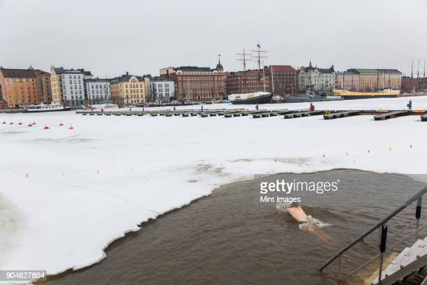 Man swimming in the icy waters of a harbour, rows of houses and sailing ship on other side of water.