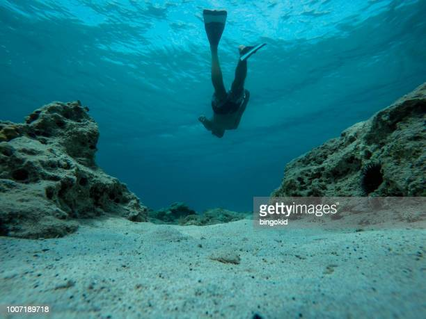 Man swimming over sea bottom