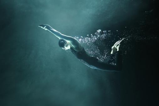 Man swimming underwater on black background - gettyimageskorea