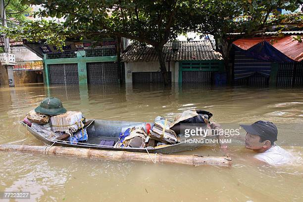 A man swims as he pushes a boat carrying his belongings in a flooded street in Thach Thanh district in the central province of Thanh Hoa 08 October...