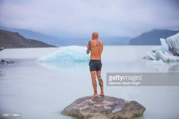 a man swims in the icy glacial waters of mount cook national park. - halbbekleidet stock-fotos und bilder