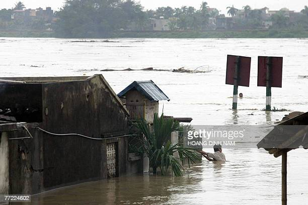 A man swims next to flooded houses along the banks of the Ma river in the central province of Thanh Hoa 05 October 2007 after Typhoon Lekima hit the...