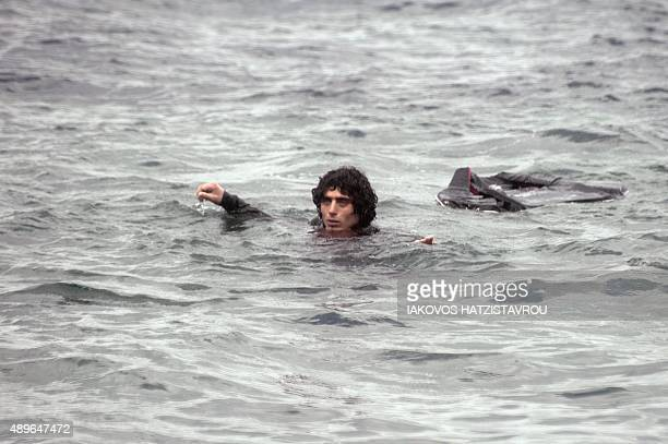 A man swims to shore after a dingy carying migrants and refugees arrives at the beach in Sykamia west of the port of Mytilene on the Greek island of...