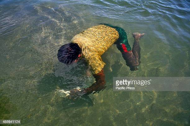 A man swims underwater to collect stones at Piain River Stone collection from underwater during summer is one of the people's livelihood in Sylhet...