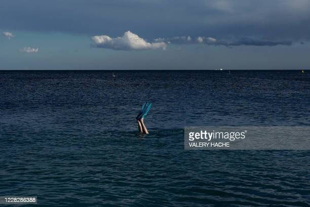 Man swims with fins in the Mediterranean Sea in the French riviera city of Nice on August 31, 2020.