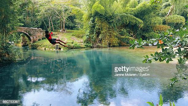 man swinging above calm river - montego bay stock pictures, royalty-free photos & images