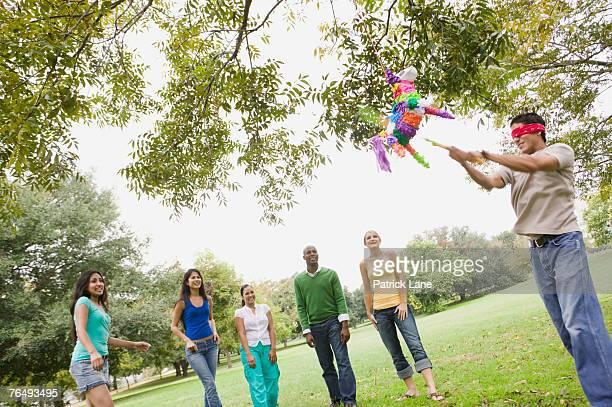 man swinging at a pinata - pinata stock pictures, royalty-free photos & images