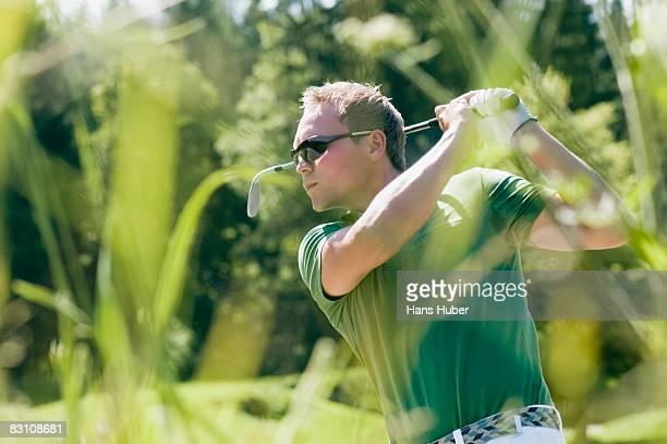 Man swinging golf club, looking away