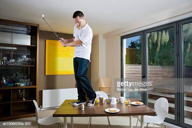 Man swinging golf club on dining table