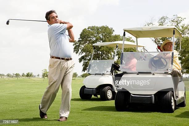 man swinging golf club - チノパンツ ストックフォトと画像