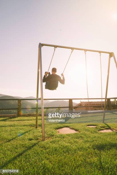 Man swinging on a swing on the mountain during sunset