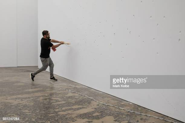 A man swings a baseball bat at the wall as he interacts with the artwork 'Constellations' by artist Marco Fusinato which is part of the 31st Biennale...