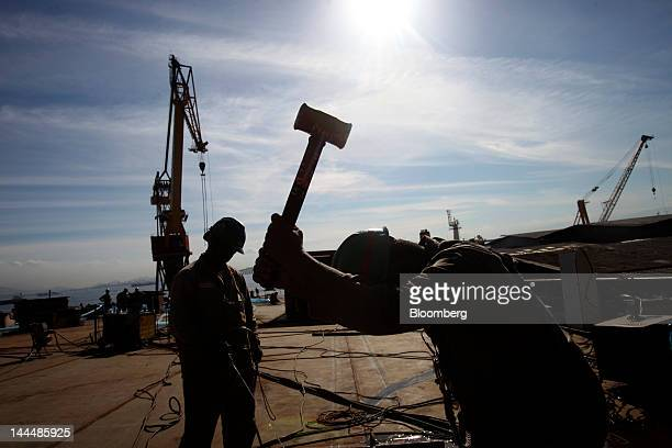 A man swings a hammer while working on the deck of a Petroleo Brasileiro SA oil tanker under construction at the Maua SA shipyard in Niteroi Brazil...