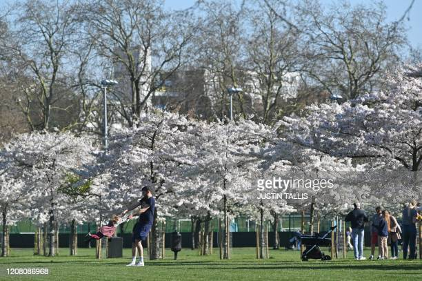 A man swings a little girl as they play in front of the blossom in Battersea Park in London on March 24 2020 after Britain's government ordered a...